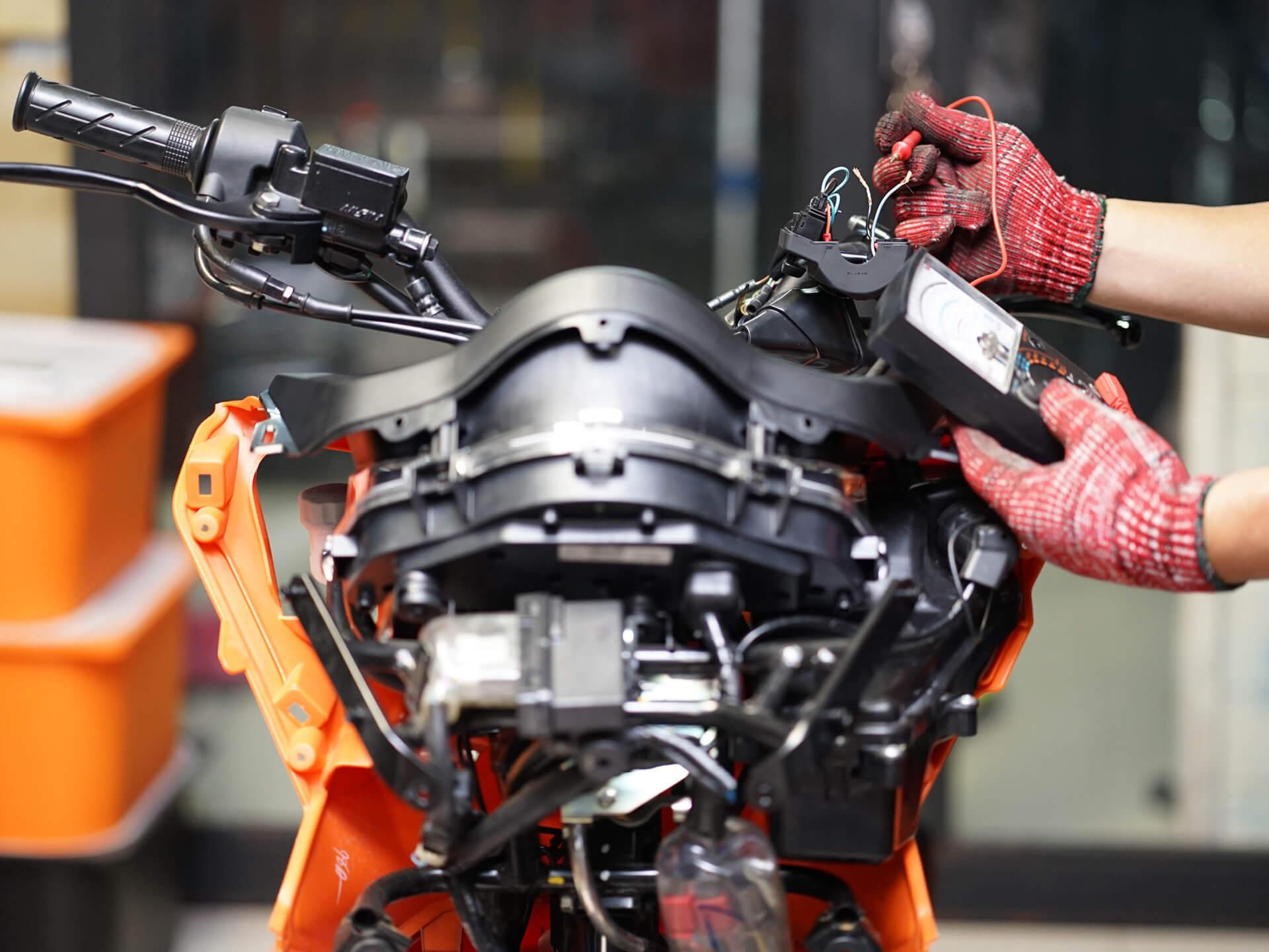 KFZ-Mechaniker testet eine Motorradbatterie